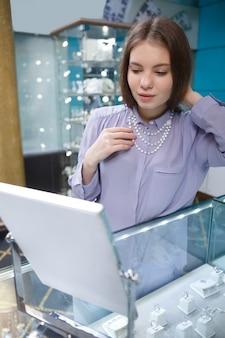 Vrouwelijke klant probeert op diamanten halsketting bij juwelier