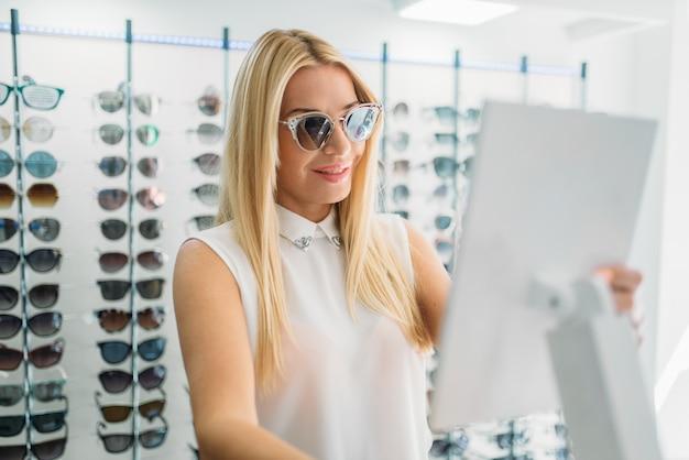 Vrouwelijke klant shoos zonnebril in optica winkel