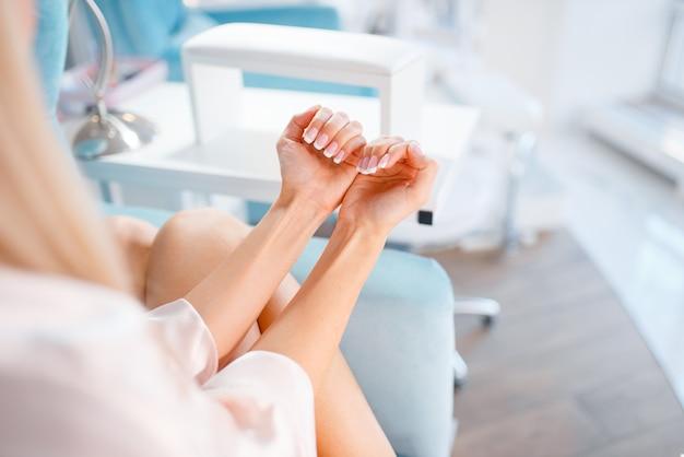 Vrouwelijke klant toont nagels in schoonheidssalon.