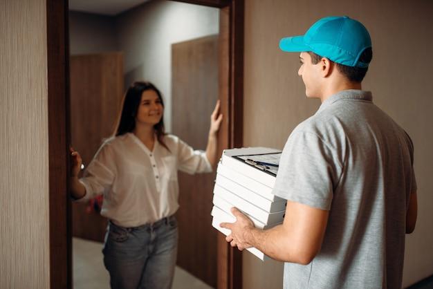 Vrouwelijke klant voor de deur en pizzakoerier