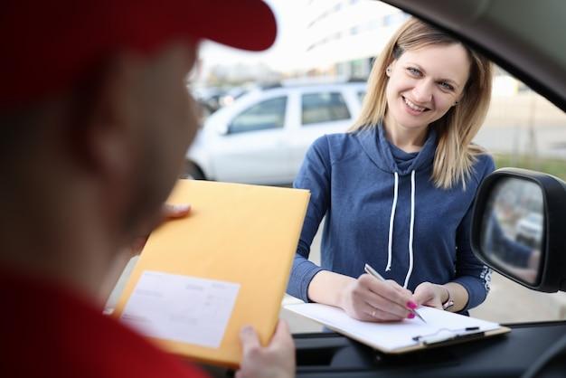 Vrouwelijke klant zet handtekening op documenten bij ontvangst van pakket van koerier
