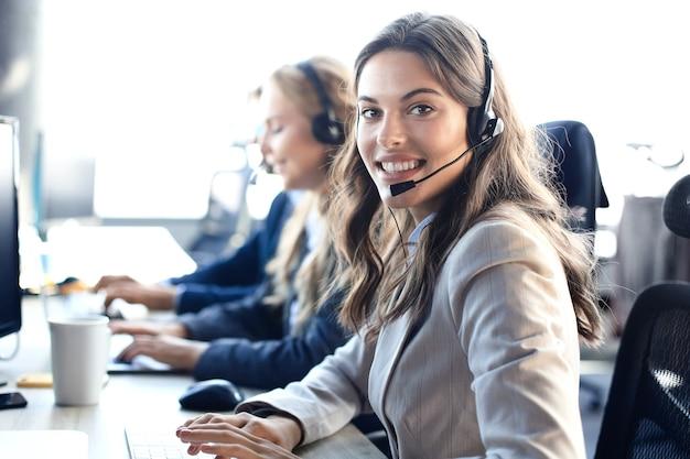 Vrouwelijke klantenondersteuningsoperator met headset en glimlachen, met collega's op de achtergrond.