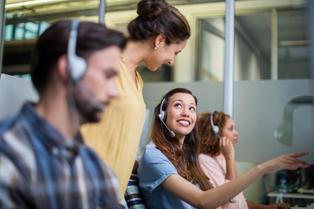 Vrouwelijke klantenservice uitvoerende interactie met haar collega aan balie
