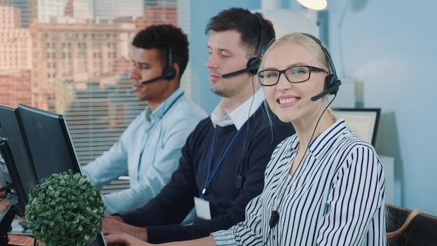 Vrouwelijke klantenservice werken in drukke callcenter.