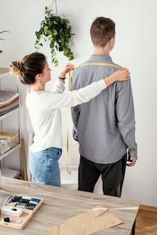 Vrouwelijke kleermaker die het overhemd van mannelijke klanten meet