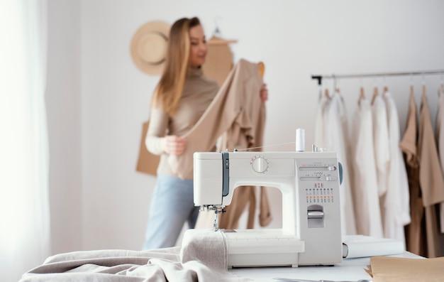 Vrouwelijke kleermaker die in de studio met naaimachine werkt
