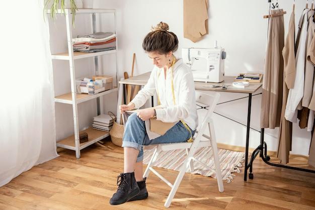 Vrouwelijke kleermaker die in de studio werkt