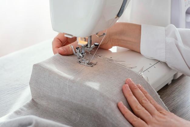 Vrouwelijke kleermaker die met naaimachine werkt