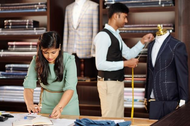 Vrouwelijke kleermaker die planner controleert wanneer haar collega op maat gemaakte colbert meet