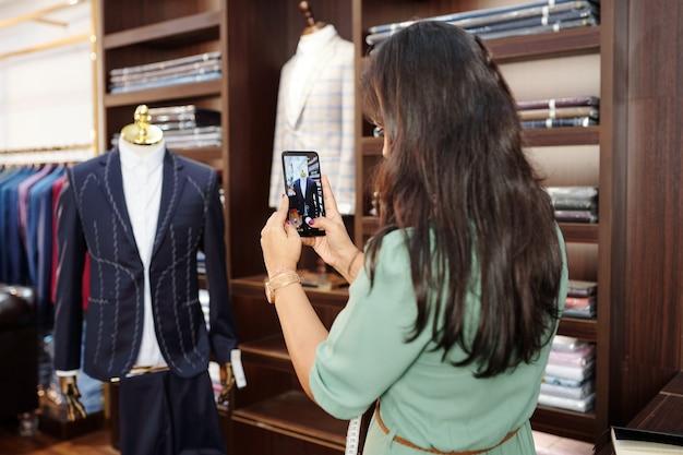 Vrouwelijke kleermaker fotograferen bijna klaar op maat gemaakte colbert op mannequin