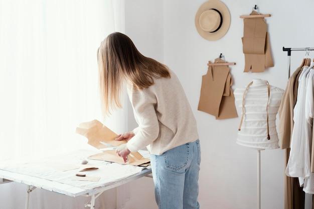 Vrouwelijke kleermaker in de studio met kleren