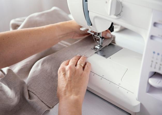 Vrouwelijke kleermaker met behulp van naaimachine