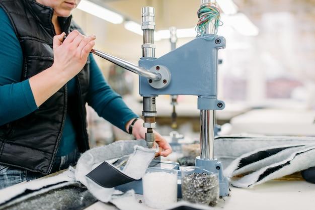 Vrouwelijke kleermaker werkt aan machine in werkplaats, kleding stof klinken. kleermakerij. uitrusting op kledingfabriek, professioneel maatwerk