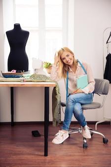 Vrouwelijke kleermaker zit op haar werkplek met laptop