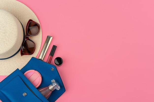 Vrouwelijke kleine handtas vol cosmetische producten op heldere roze achtergrond