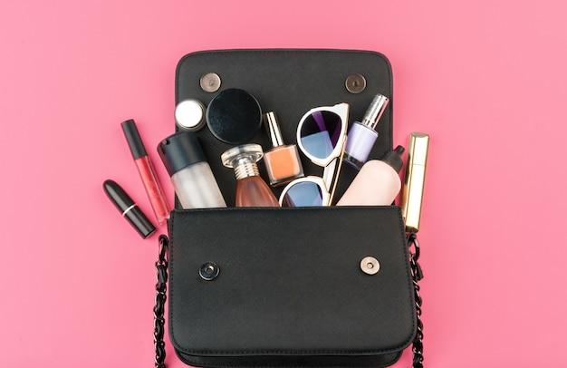 Vrouwelijke kleine handtas vol cosmetische producten