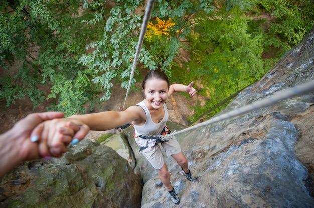 Vrouwelijke klimmer die duim opgeeft en op hoge rots glimlacht. man die een hand geeft aan de vrouw.