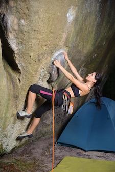 Vrouwelijke klimmer die grote kei in aard met kabel beklimt