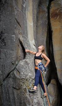 Vrouwelijke klimmer die met kabel op een rotsachtige muur beklimt