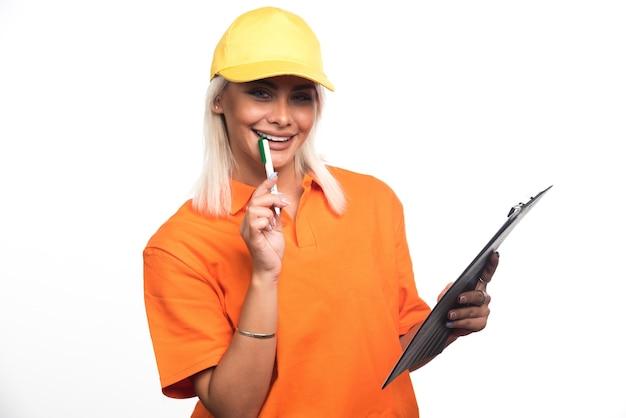 Vrouwelijke koerier bedrijf notebook op witte achtergrond tijdens het glimlachen. hoge kwaliteit foto