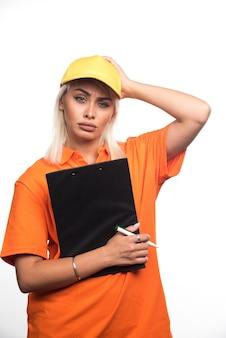 Vrouwelijke koerier bedrijf order notebook op witte achtergrond. hoge kwaliteit foto