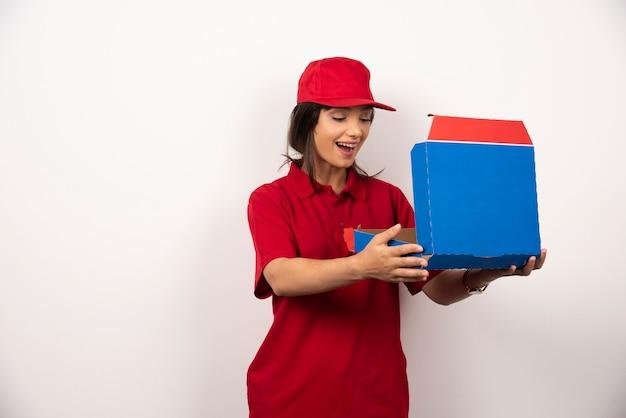 Vrouwelijke koerier die een doos pizza opent