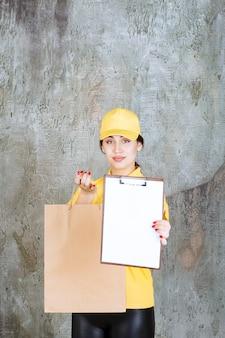 Vrouwelijke koerier die een geel uniform draagt, levert een kartonnen boodschappentas af en presenteert de blanco ter ondertekening.