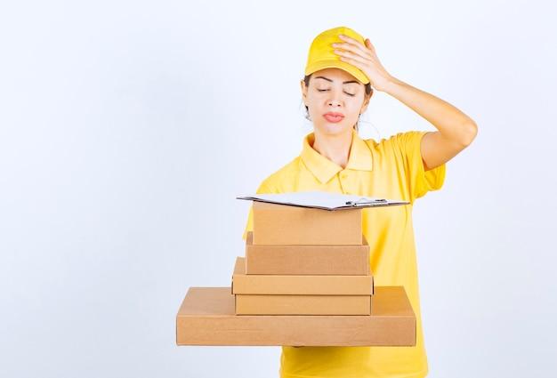 Vrouwelijke koerier die een voorraad kartonnen dozen levert en moeite heeft om het adres te vinden.