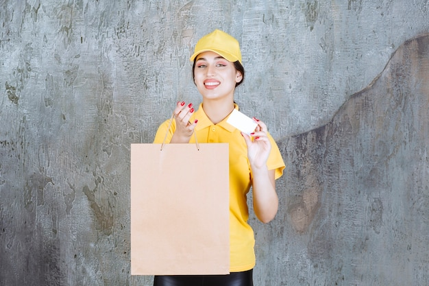 Vrouwelijke koerier die gele uniform draagt die een kartonnen boodschappentas levert en haar visitekaartje presenteert.