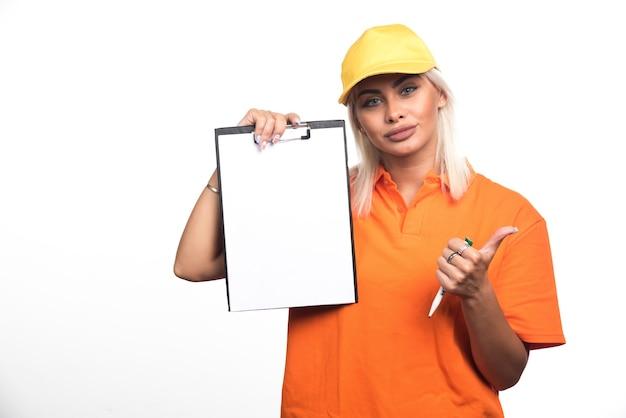 Vrouwelijke koerier die leeg notitieboekje op witte achtergrond houdt die duimen toont. hoge kwaliteit foto