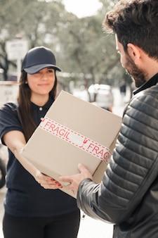Vrouwelijke koerier die pakket leveren aan de mens