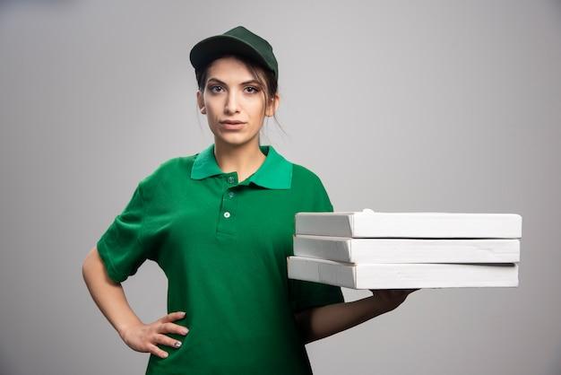 Vrouwelijke koerier die pizzadozen houdt