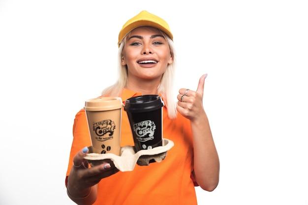 Vrouwelijke koerier die twee kopjes koffie op witte achtergrond houdt terwijl duimen opdagen. hoge kwaliteit foto