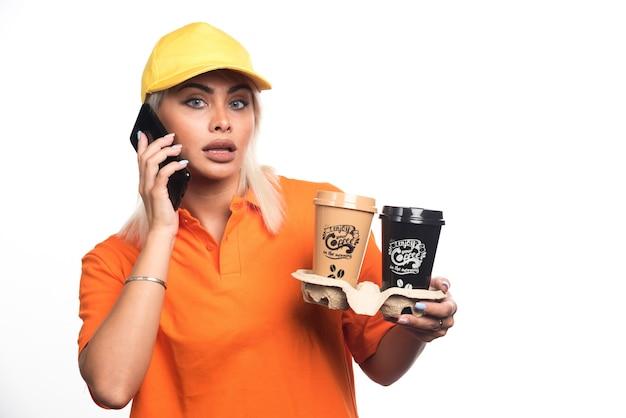 Vrouwelijke koerier die twee kopjes koffie op witte achtergrond houdt tijdens het gesprek met de telefoon. hoge kwaliteit foto