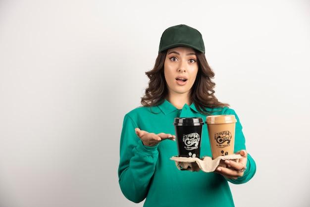 Vrouwelijke koerier die vraagt wat te doen met koffiekopjes.