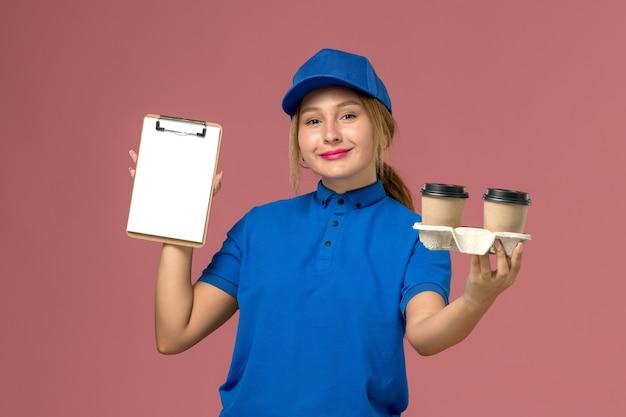 Vrouwelijke koerier in blauw uniform bedrijf levering kopjes koffie en blocnote met glimlach op roze, service job werknemer uniforme levering