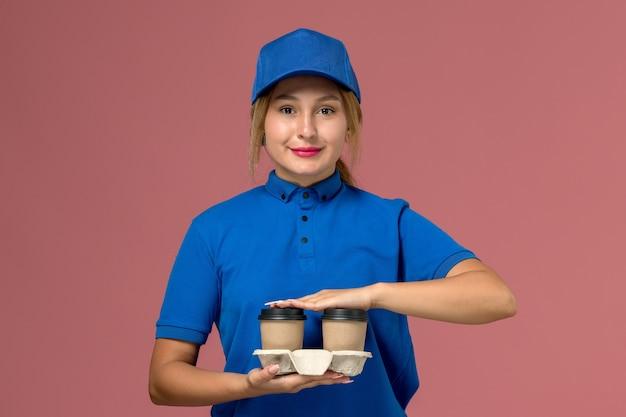 Vrouwelijke koerier in blauw uniform bedrijf levering kopjes koffie glimlachend op roze, service uniforme levering baan
