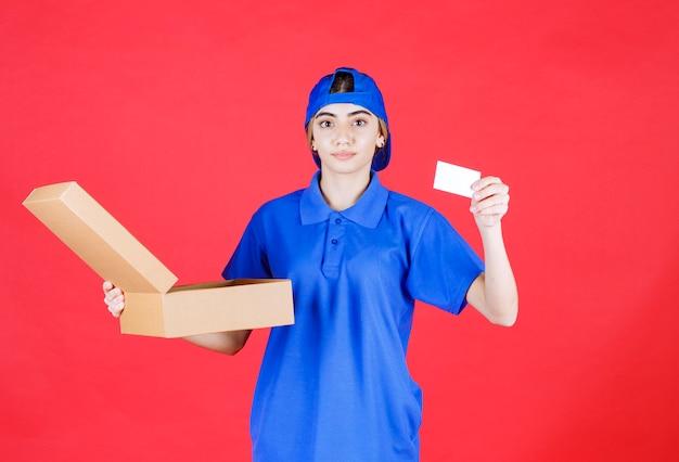 Vrouwelijke koerier in blauw uniform die een kartonnen afhaaldoos houdt en haar visitekaartje voorstelt.