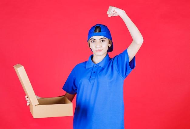 Vrouwelijke koerier in blauw uniform die een kartonnen afhaaldoos vasthoudt en haar armspier toont.