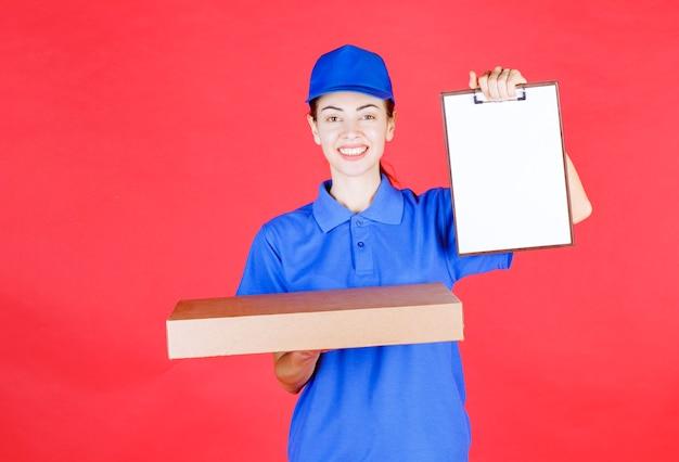 Vrouwelijke koerier in blauw uniform die een kartonnen afhaalpizzadoos vasthoudt en de handtekeninglijst presenteert.