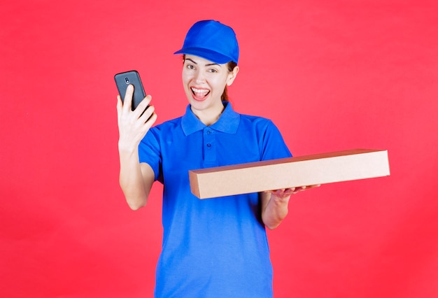 Vrouwelijke koerier in blauw uniform die een kartonnen afhaalpizzadoos vasthoudt en haar selfie neemt.