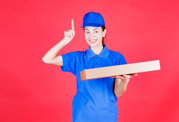 Vrouwelijke koerier in blauw uniform die een kartonnen afhaalpizzadoos vasthoudt en verward denkt of kijkt.