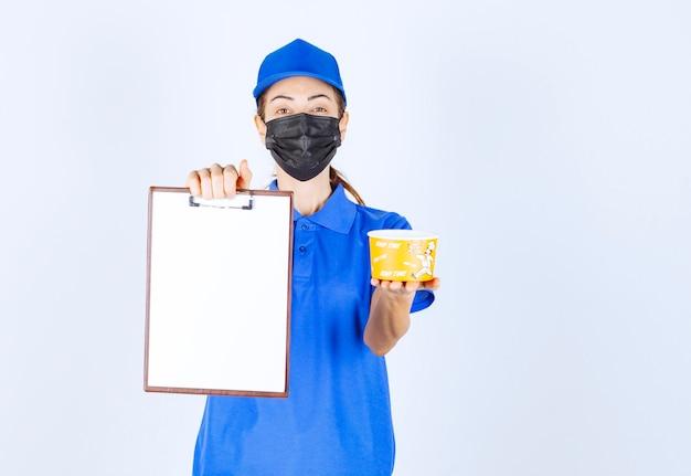 Vrouwelijke koerier in blauw uniform en gezichtsmasker die een afhaalmaaltijd levert en de klant vraagt om te ondertekenen.