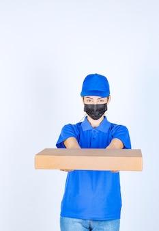 Vrouwelijke koerier in blauw uniform en gezichtsmasker die een kartonnen doos aan de klant levert.
