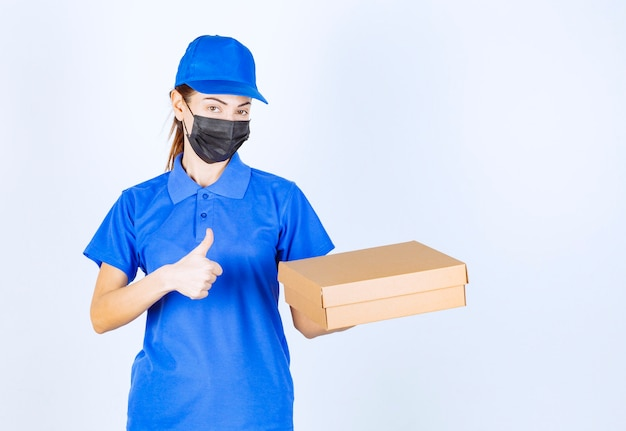 Vrouwelijke koerier in blauw uniform en gezichtsmasker die een kartonnen doos vasthoudt en een handteken voor plezier toont.