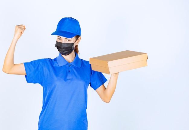 Vrouwelijke koerier in blauw uniform en gezichtsmasker die een kartonnen doos vasthoudt en haar vuist laat zien.