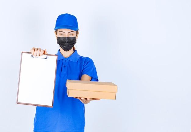 Vrouwelijke koerier in blauw uniform en gezichtsmasker die een kartonnen pakket levert en de klant vraagt om op de blanco te tekenen.
