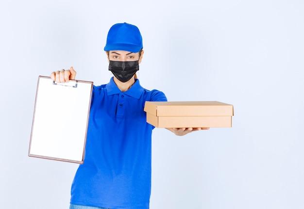 Vrouwelijke koerier in blauw uniform en gezichtsmasker die een kartonnen pakket levert en de klant vraagt om op de blanco te tekenen. Gratis Foto