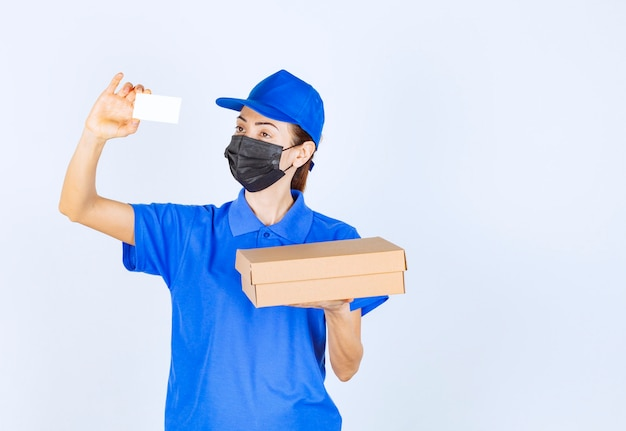 Vrouwelijke koerier in blauw uniform en gezichtsmasker die een kartonnen pakket levert en haar visitekaartje presenteert.