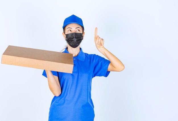 Vrouwelijke koerier in blauw uniform en gezichtsmasker met een kartonnen doos en ergens naar wijzend.